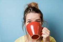 Retrato de la mujer joven hermosa con una taza roja en un backg azul Fotografía de archivo libre de regalías