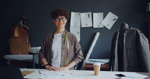 Retrato de la mujer joven hermosa del diseñador de moda acertado en taller almacen de video