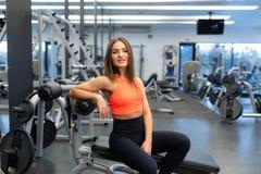 Retrato de la mujer joven hermosa delgada relajarse en gimnasio despu?s del entrenamiento duro imagen de archivo
