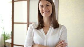 Retrato de la mujer joven hermosa en la blusa blanca que se coloca en los brazos sonrientes de la sala de estar cruzados almacen de metraje de vídeo