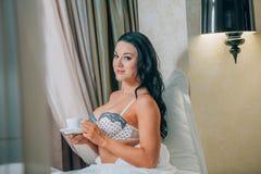 Retrato de la mujer joven hermosa en la camisa de dormir que sostiene la taza de café en cama Imagenes de archivo