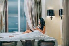 Retrato de la mujer joven hermosa en la camisa de dormir que sostiene la taza de café en cama Imagen de archivo