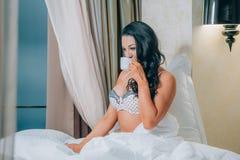 Retrato de la mujer joven hermosa en la camisa de dormir que sostiene la taza de café en cama Foto de archivo libre de regalías