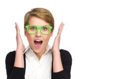 Retrato de la mujer joven hermosa en los vidrios verdes que parecen sorprendidos. Imagenes de archivo