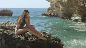 Retrato de la mujer joven hermosa en la playa rocosa salvaje metrajes
