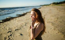 Retrato de la mujer joven hermosa que habla en el teléfono un fondo del mar Muchacha que mira puesta del sol Imagen de archivo