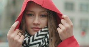 Retrato de la mujer joven hermosa que lleva la capilla roja que sonríe a una cámara almacen de metraje de vídeo
