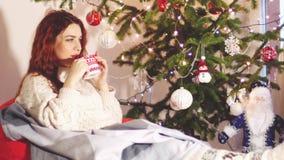 Retrato de la mujer joven hermosa que lleva el suéter elegante de la Navidad y de los calcetines que se sientan en té cómodo del  almacen de video