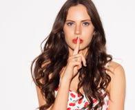 Retrato de la mujer joven hermosa que señala el finger a sus labios sobre el fondo blanco Secreto silencioso del concepto indoor  imagen de archivo