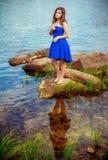 Retrato de la mujer joven hermosa que se coloca en una orilla del río Fotografía de archivo libre de regalías