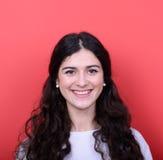 Retrato de la mujer joven hermosa que sonríe contra fondo rojo Imagen de archivo