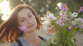 Retrato de la mujer joven hermosa que sonríe y que sostiene el ramo de flores salvajes almacen de video