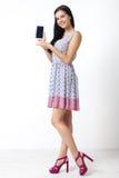 Retrato de la mujer joven hermosa que sostiene smartphone en el fondo blanco Foto de archivo libre de regalías