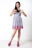Retrato de la mujer joven hermosa que sostiene smartphone en el fondo blanco Fotos de archivo libres de regalías