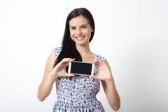 Retrato de la mujer joven hermosa que sostiene smartphone en el fondo blanco Imágenes de archivo libres de regalías