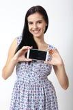 Retrato de la mujer joven hermosa que sostiene smartphone en el fondo blanco Foto de archivo