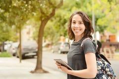 Retrato de la mujer joven hermosa que usa la tableta al aire libre Fotografía de archivo