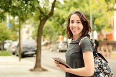 Retrato de la mujer joven hermosa que usa la tableta al aire libre Imagenes de archivo