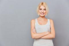 Retrato de la mujer joven hermosa sonriente que se coloca con los brazos cruzados Foto de archivo libre de regalías