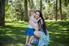Retrato de la mujer joven hermosa sonriente y de su pequeña hija que se sientan en hierba fotos de archivo