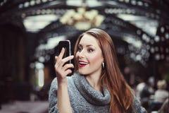 Retrato de la mujer joven hermosa sorprendida que mira su smartphone Fotografía de archivo libre de regalías