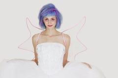 Retrato de la mujer joven hermosa vestida como ángel con el pelo teñido contra fondo gris Imagen de archivo libre de regalías