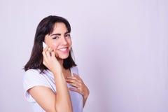 Retrato de la mujer joven hispánica que usa un teléfono móvil foto de archivo libre de regalías