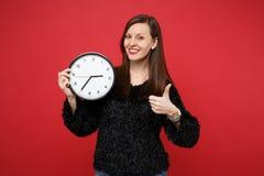 Retrato de la mujer joven imponente en pulgar negro de la demostración del suéter de la piel para arriba, sosteniendo el reloj re fotografía de archivo