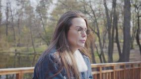 Retrato de la mujer joven linda en la situación de la chaqueta de los vaqueros en el puente de madera que mira alrededor y in cam almacen de metraje de vídeo