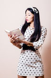 Retrato de la mujer joven linda morena hermosa en el libro de lectura blanco del vestido del lunar en la imagen blanca del fondo Fotos de archivo