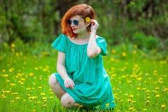Retrato de la mujer joven linda que se relaja en parque de la primavera Fotografía de archivo