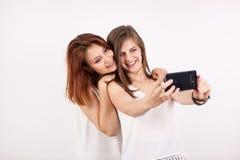 Retrato de la mujer joven magnífica dos, de un redhair y de un moreno, tomando un selfie Fotografía de archivo libre de regalías