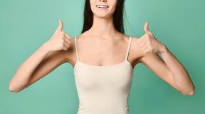 Retrato de la mujer joven de moda que muestra el pulgar para arriba sobre fondo gris imagenes de archivo