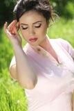 Retrato de la mujer joven morena hermosa que descansa sobre GR verde Imagen de archivo