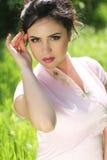 Retrato de la mujer joven morena hermosa que descansa sobre GR verde Fotografía de archivo libre de regalías