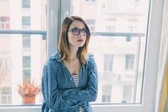 Retrato de la mujer joven pensativa hermosa en vidrios Foto de archivo libre de regalías