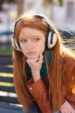 Retrato de la mujer joven pensativa triste hermosa en auriculares Fotos de archivo