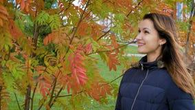 Retrato de la mujer joven preciosa y hermosa feliz en bosque en colores de la caída la muchacha ríe la situación de un arbusto de almacen de video