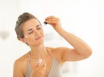 Retrato de la mujer joven que aplica el elixir cosmético Fotos de archivo