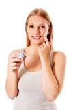 Retrato de la mujer joven que aplica la crema de la crema hidratante en su cara bonita Fotos de archivo libres de regalías