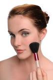 Retrato de la mujer joven que aplica maquillaje Fotos de archivo libres de regalías