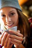 Retrato de la mujer joven que bebe el café caliente Foto de archivo