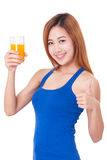 Retrato de la mujer joven que bebe el zumo de naranja Imagenes de archivo