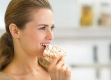 Retrato de la mujer joven que come el pan quebradizo fotos de archivo libres de regalías