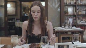 Retrato de la mujer joven que corta el filete sabroso que miente con las verduras y las hojas en la placa en el restaurante Alcoh metrajes