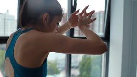 Retrato de la mujer joven, que está estirando sus brazos y músculos del hombro en gimnasio almacen de metraje de vídeo