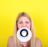 Retrato de la mujer joven que grita con un megáfono contra amarillo Fotos de archivo