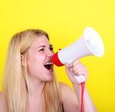 Retrato de la mujer joven que grita con un megáfono contra amarillo Fotografía de archivo