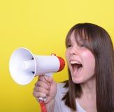 Retrato de la mujer joven que grita con un megáfono contra amarillo Imagen de archivo libre de regalías