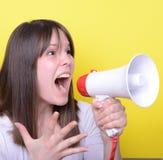 Retrato de la mujer joven que grita con un megáfono contra amarillo Foto de archivo